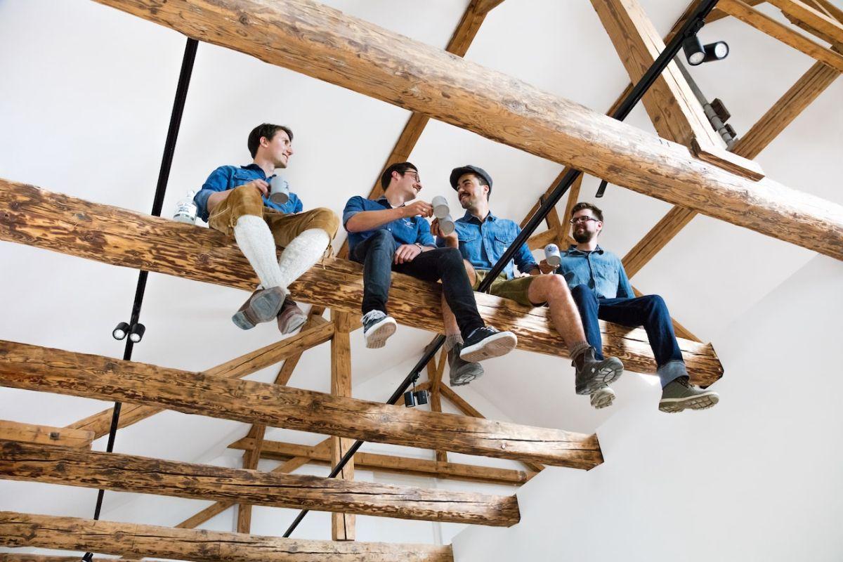 THE DUKE Gründer Max und Mitarbeiter auf Holzbalken