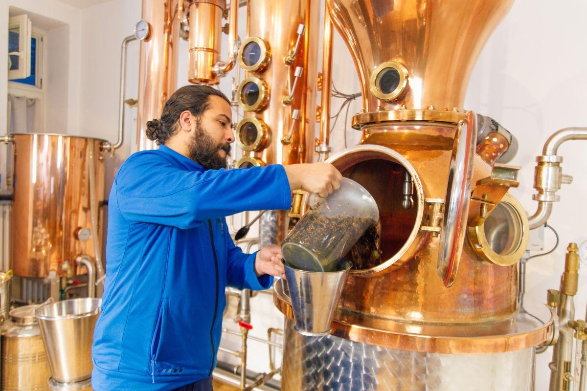 THE DUKE Destillateur füllt das Mazarat in die Kupferblase