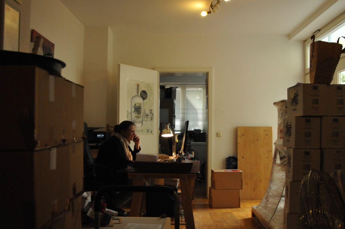 Mitarbeiterin der THE DUKE Destillerie am Schreibtisch, eingekesselt von Kartons
