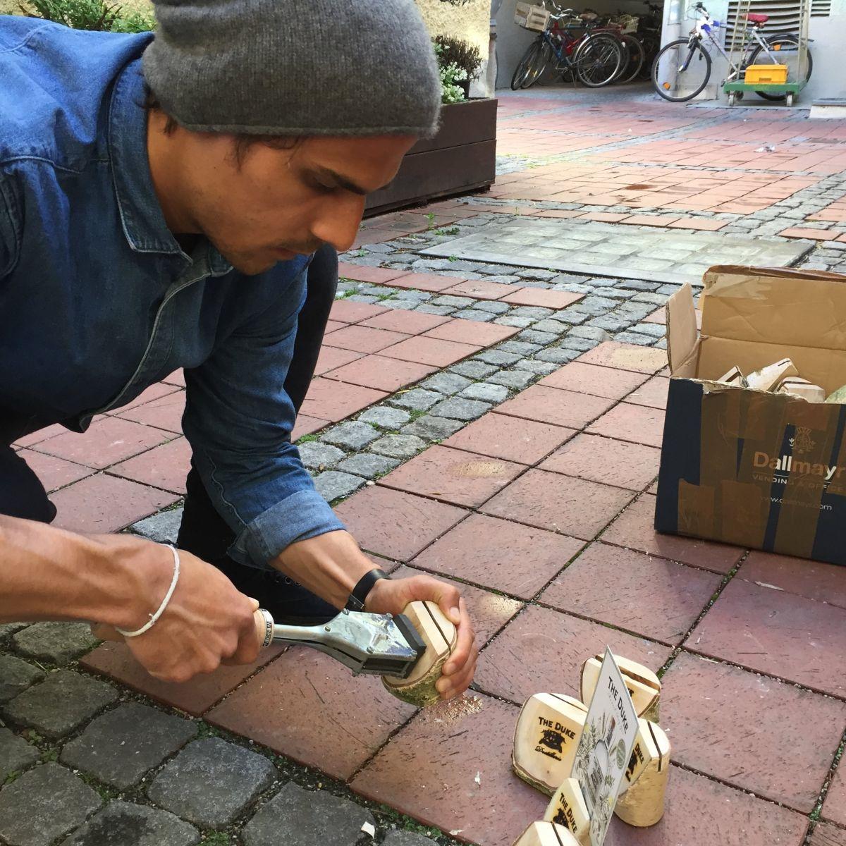Mitarbeiter der THE DUKE Destillerie setzt ein Brandlogo auf Holzaufsteller
