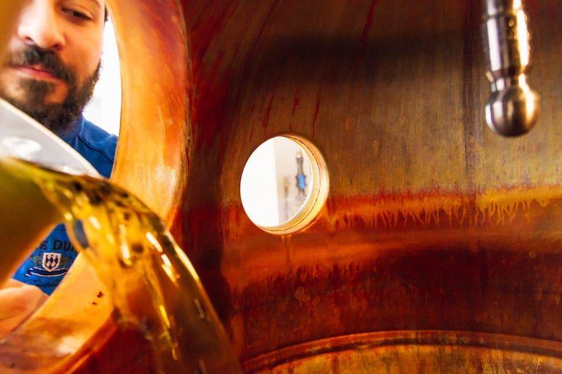 Der THE DUKE Destillateur füllt das Mazarat durch das Mannloch in die Kupferblase