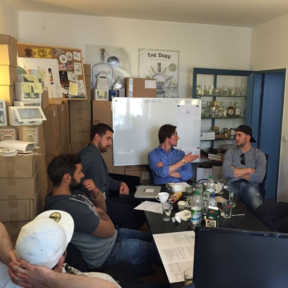Gründer Max und die Mitarbeiter der THE DUKE Destillerie halten ein Meeting ab - eingekesselt von Kartons