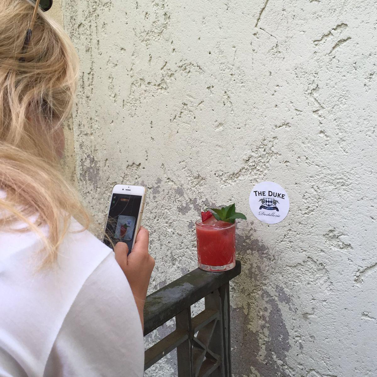 THE DUKE Mitarbeiterin macht ein Foto eines Drinks im Hinterhof der Destillerie