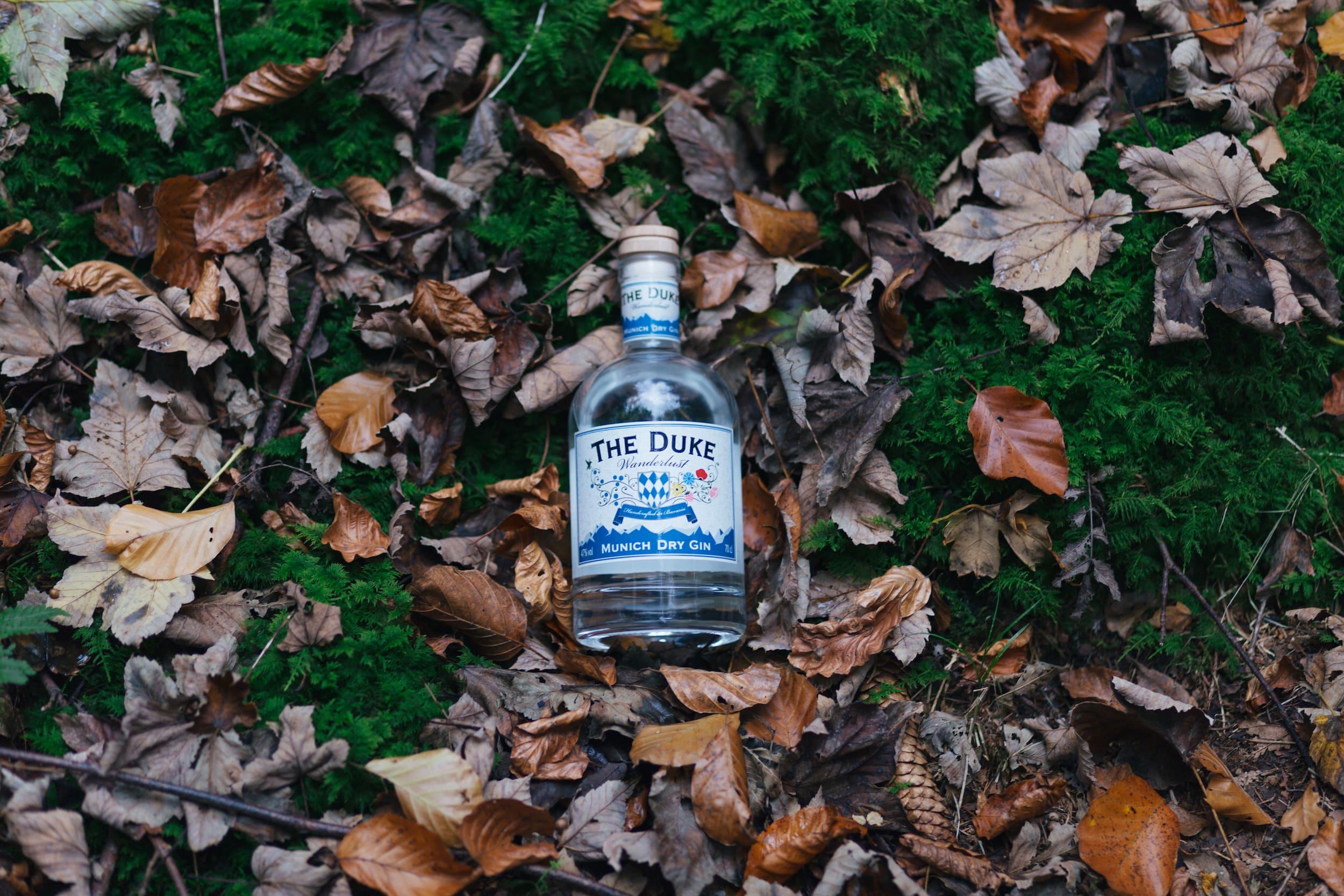 Eine Flasche THE DUKE Wanderlust Gin liegt im Wald auf Laub