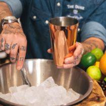 Guy beim Cocktails mixen im Kupfer Shaker
