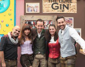 Das Team von Bodo's Cafézelt vor THE DUKE Gin Bar Schild