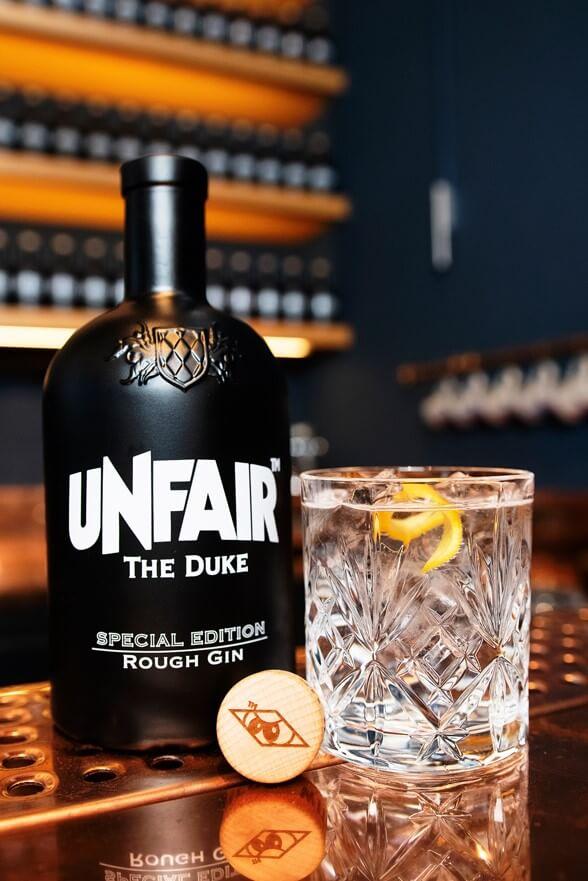 Gin Tonic, schwarze THE DUKE Gin Flasche mit weißem Unfair Athletics Logo