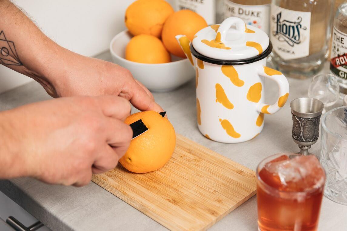 mit Messer Zeste aus Orange schneiden
