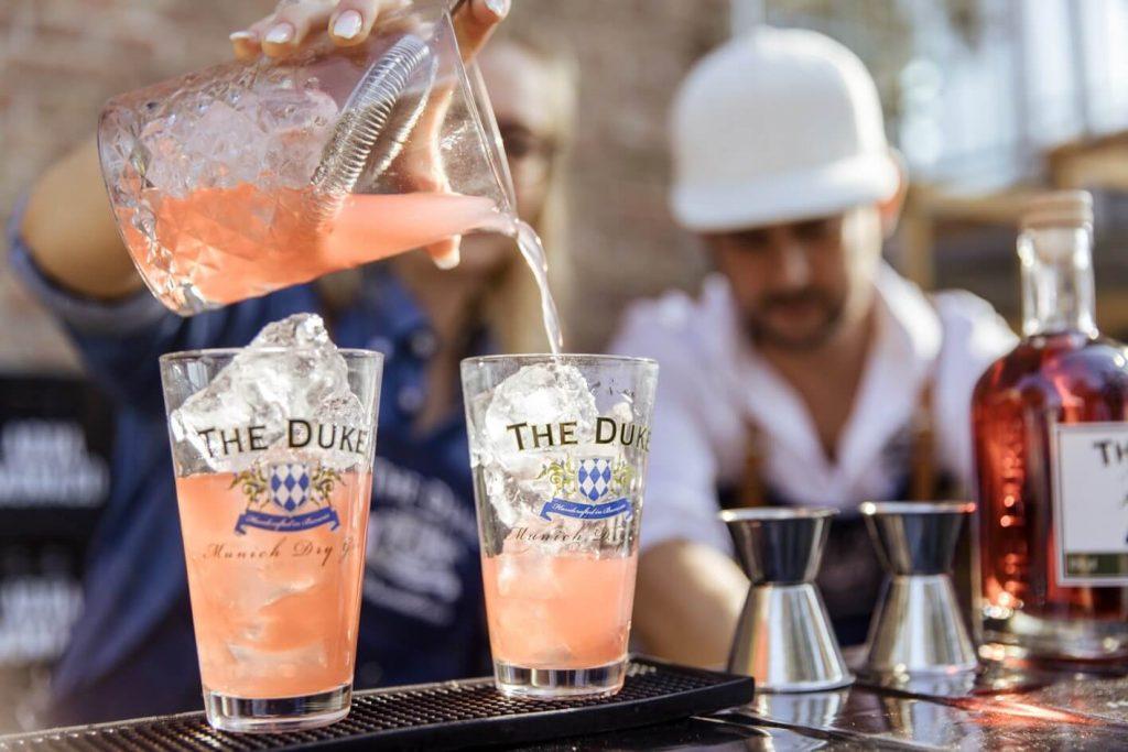 Barkeeper der THE DUKE Destillerie schenkt einen Pink Gin & Tonic Drink ein
